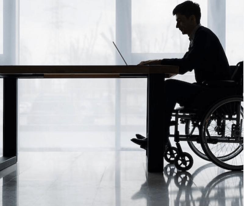 hombre en silla de ruedas frente a una mesa