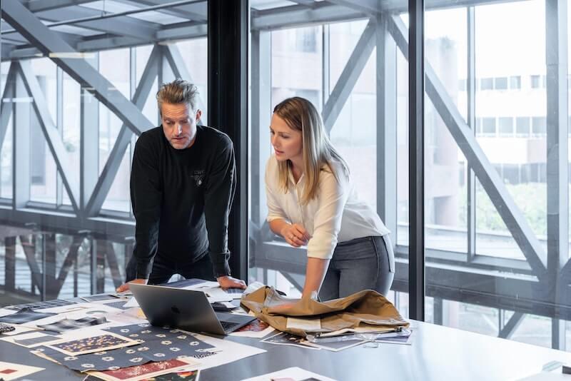 hombre y mujer trabajan con telas en oficina