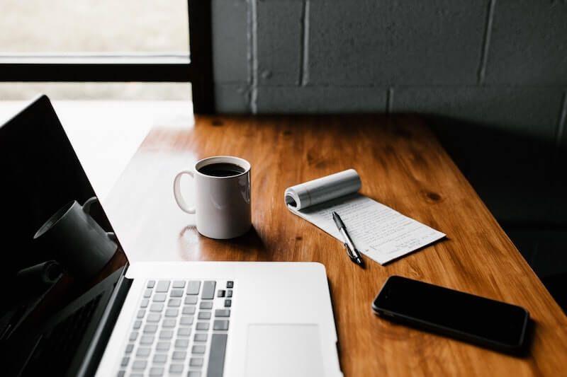 laptop taza cafe libreta movil
