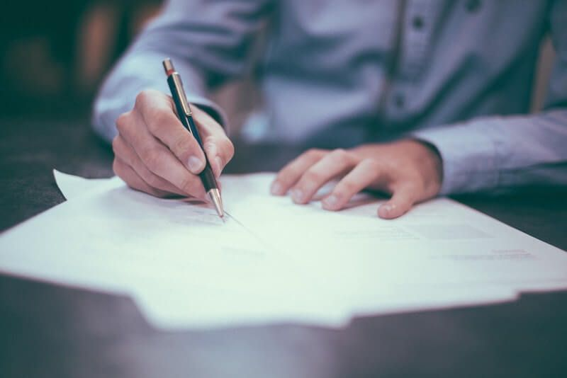 hombre camisa azul firmando papeles