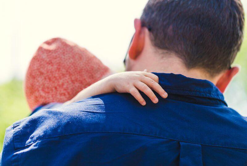 hombre camisa azul con su hijo en brazos