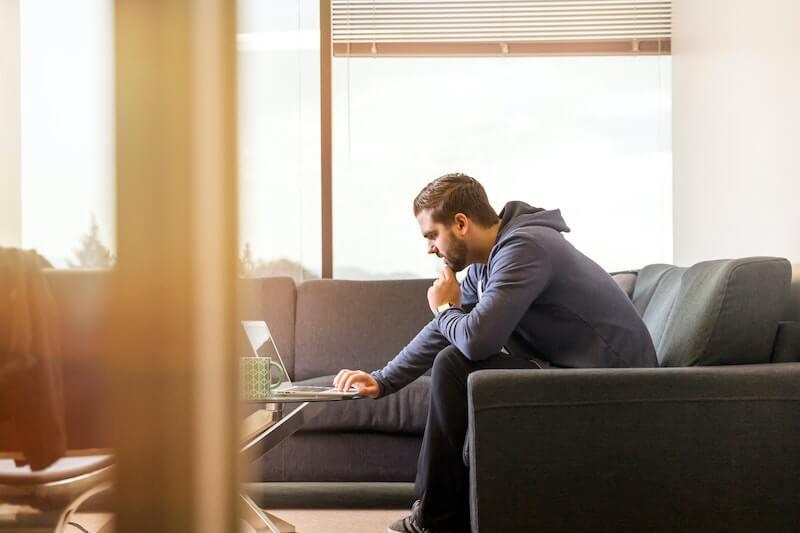 hombre sentado en soca frente al ordenador
