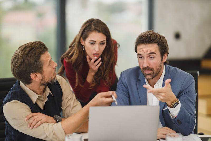 grupo de trabajo mirando portátil sorprendidos