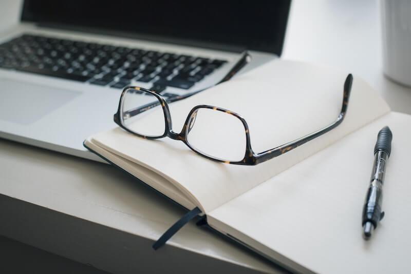 gafas sobre libreta y laptop