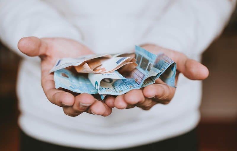 manos llenas de billetes de euro