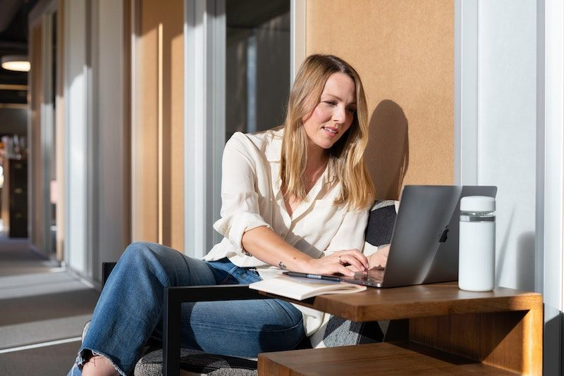 chica joven rubia con laptop al sol