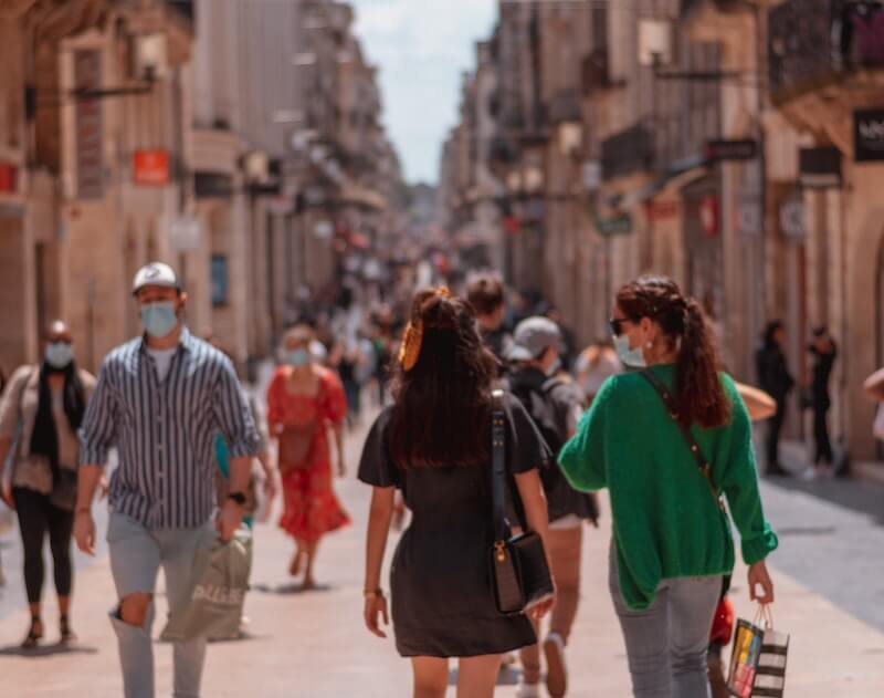 personas paseando en la ciudad con mascarilla