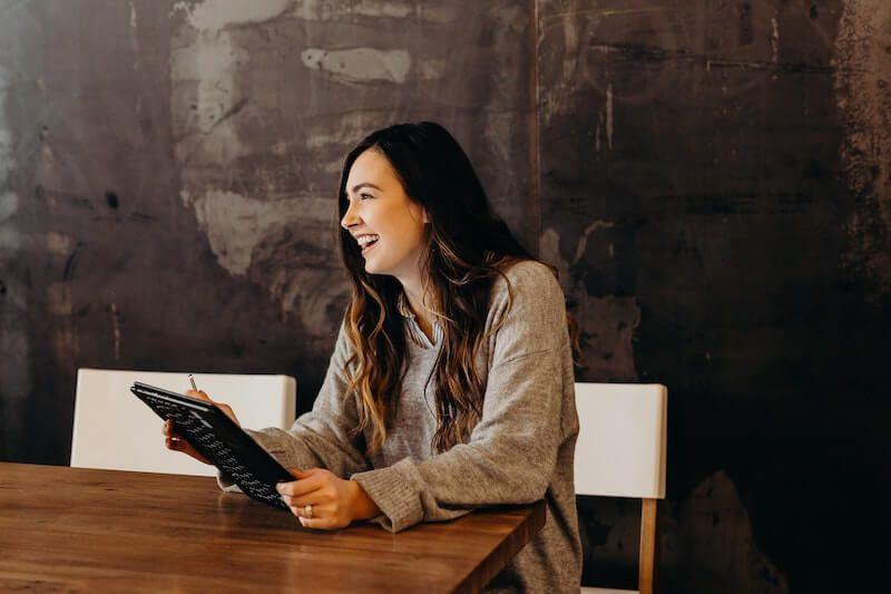 mujer joven rie sentada a la mesa